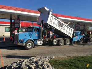 dump truck and paver install asphalt at convenience store