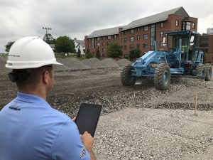 project manager looking at tablet while grader installs stone subbase