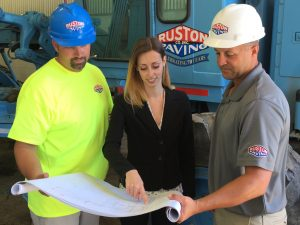 Woman looking at plans with project manager and laborer
